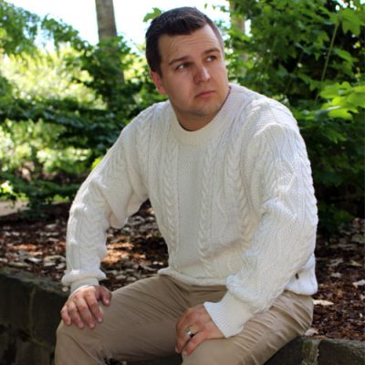 A traditional Aran Knit jumper featuring intricate cables in white magnolia colour
